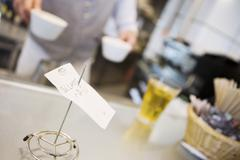 Waiter serving beverages in cafe, focus on check stub holder in foreground, c Stock Photos