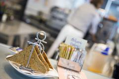 Waiter working in cafe, focus on toast rack in foreground, close-up (tilt) Stock Photos