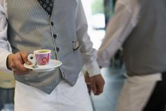Two waiters working in cafe, man carrying expresso cup and saucer, mid-sectio Stock Photos