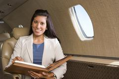 businesswoman with folder on aeroplane, smiling, close-up - stock photo