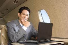 businessman using laptop computer on aeroplane, smiling, close-up - stock photo