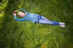 teenage girl (11-13) lying in grass with eyes closed, elevated view (full fra - stock photo