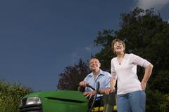 senior woman standing next to man on riding lawn mower - stock photo