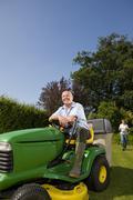 senior man sitting on riding lawn mower - stock photo