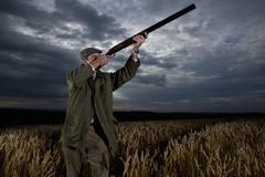 hunter aiming rifle towards sky in wheat field - stock photo