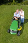 portrait of woman hugging man on riding lawn mower - stock photo