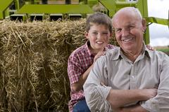 Portrait of farmer and grandson on tractor with straw Kuvituskuvat