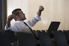 Businessman checking time on watch in empty conference room, stretching, lapt Stock Photos