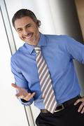 Businessman wearing mobile phone hands-free device, making hand sign, smiling Stock Photos