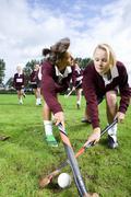 teenage girls playing field hockey - stock photo