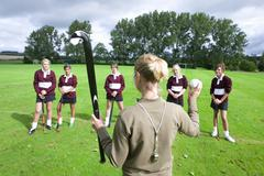 coach holding field hockey stick and ball in front of team - stock photo