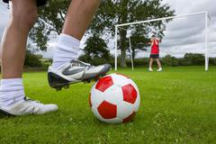close up of soccer player aiming ball at frightened goalie - stock photo