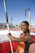 Young female pole vault athlete with pole by bar, smiling, portrait Stock Photos