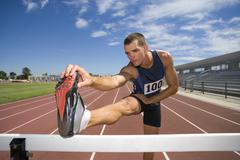 Male athlete stretching hamstrings, foot on hurdle, low angle view Stock Photos