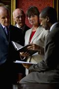 Three businessmen looking at diary of businesswoman, portrait of woman Stock Photos