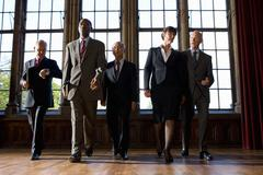 Small group of businessmen and woman walking in hall, low angle view Stock Photos
