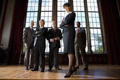 Small group of businessmen and woman in hall, portrait of woman, low angle vi Stock Photos