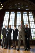 small group of businessmen and woman in hall, portrait, low angle view - stock photo