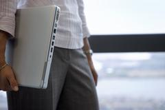 businesswoman standing beside window, carrying laptop underarm, close-up, sid - stock photo