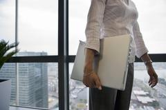 businesswoman standing beside window, carrying laptop underarm, side view, mi - stock photo