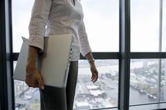 Businesswoman standing beside window, carrying laptop underarm, side view, mi Stock Photos