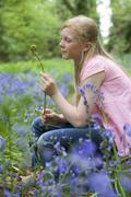 girl holding fiddlehead fern in field of bluebell flowers - stock photo