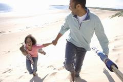 Father and daughter walking on beach, elevated view Stock Photos