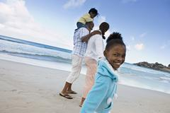 Two generation family walking on sandy beach, girl (7-9) smiling, side view,  Stock Photos
