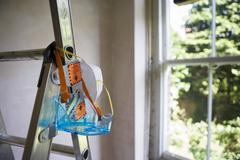 Protective safety goggles and dust mask hanging from step ladder in room besi Stock Photos