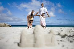 sandcastle on beach, focus on two generation family in background, portrait,  - stock photo