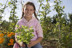 Girl (9-11) holding pot plant in garden, smiling, front view, portrait Stock Photos