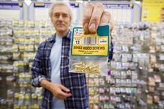 Senior man shopping for brass wood screws in diy shop, smiling, portrait, foc Stock Photos