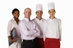 Proud restaurant manager with waitress and chefs, smiling, portrait, cut out Stock Photos