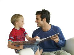 father and son looking at photo album, cut out - stock photo