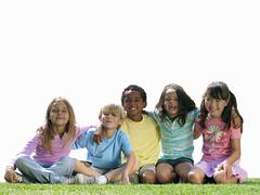 Group of children sitting on grass, smiling, portrait, cut out Stock Photos
