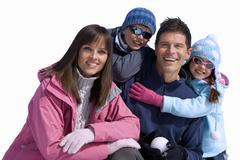 family of four wearing winter clothing, smiling, portrait, cut out - stock photo