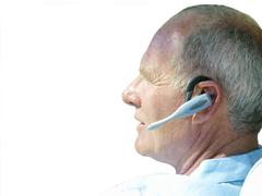 close-up of senior man talking on bluetooth, ear-piece, cut out - stock photo