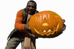 senior man holding large pumpkin, cut out - stock photo