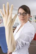 doctor putting on surgical glove with attitude in examination room - stock photo
