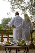 Couple in bathrobes petting cat on patio with breakfast in foreground Stock Photos