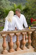 couple in bathrobes standing at balcony railing - stock photo