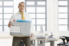 Businessman holding box of belongings in office Stock Photos