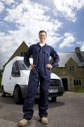 Handyman in coveralls standing with hands on hips near work van Stock Photos