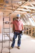 Construction worker leaning on ladder in attic Stock Photos