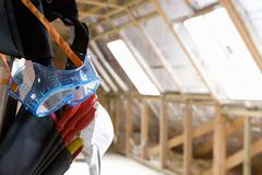 Goggles hanging from tool belt in attic Stock Photos