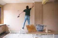 Man on step stool plastering wall in house under construction Stock Photos