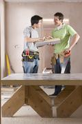 male carpenter and apprentice with tools talking next to sawhorse - stock photo