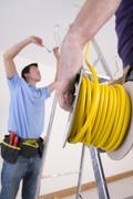 close up of electrician holding cable spool with co-worker wiring ceiling in  - stock photo