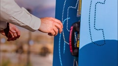 Businessman using a pay phone - stock footage