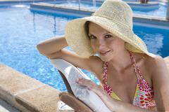 smiling woman wearing sun hat and laying on lounge chair at poolside - stock photo